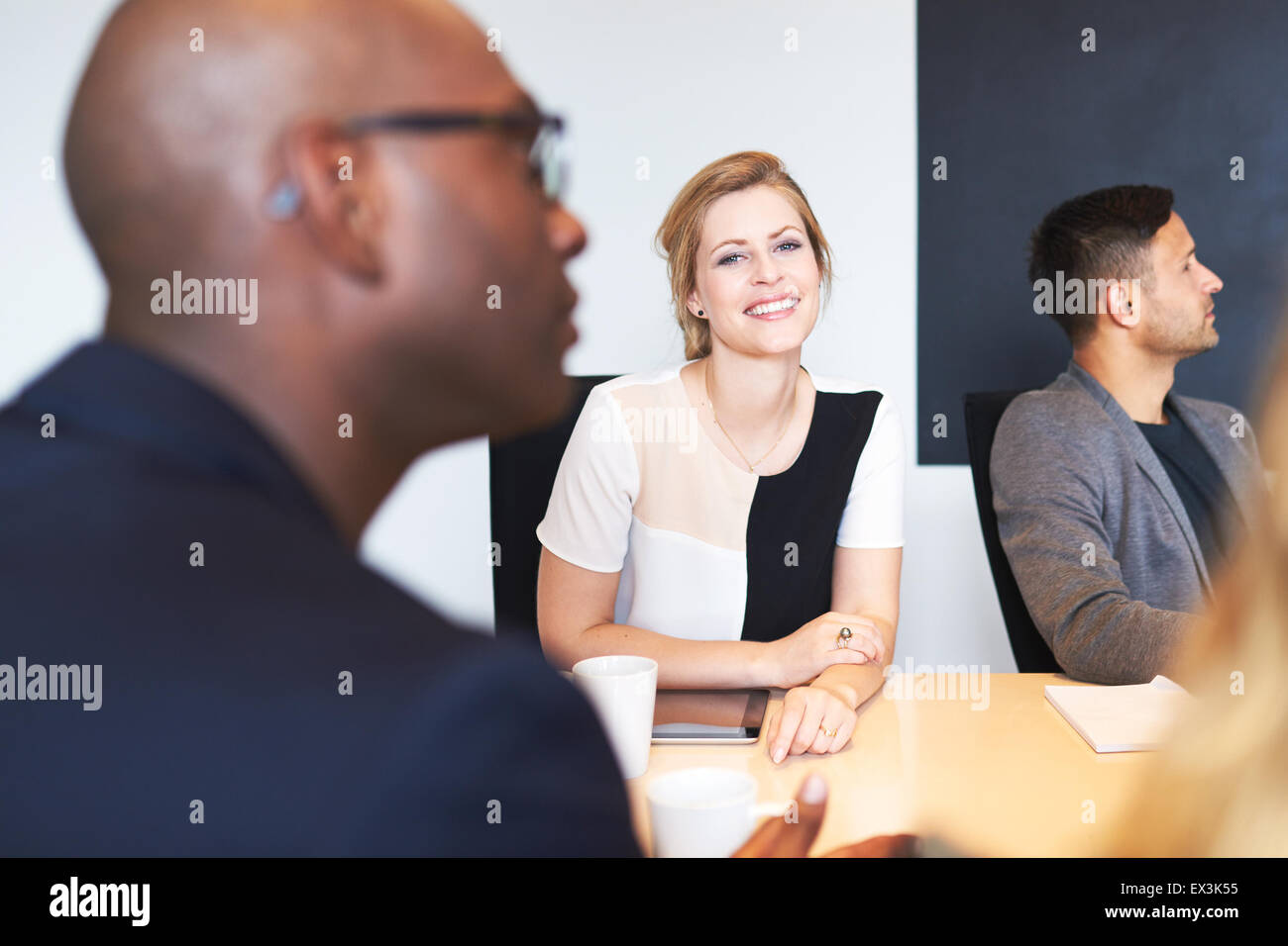 White female executive smiling at camera during a work meeting. - Stock Image