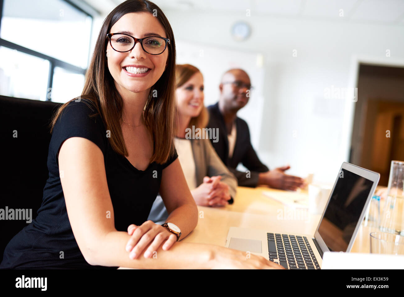 Young female white executive smiling during meeting in office conference room - Stock Image