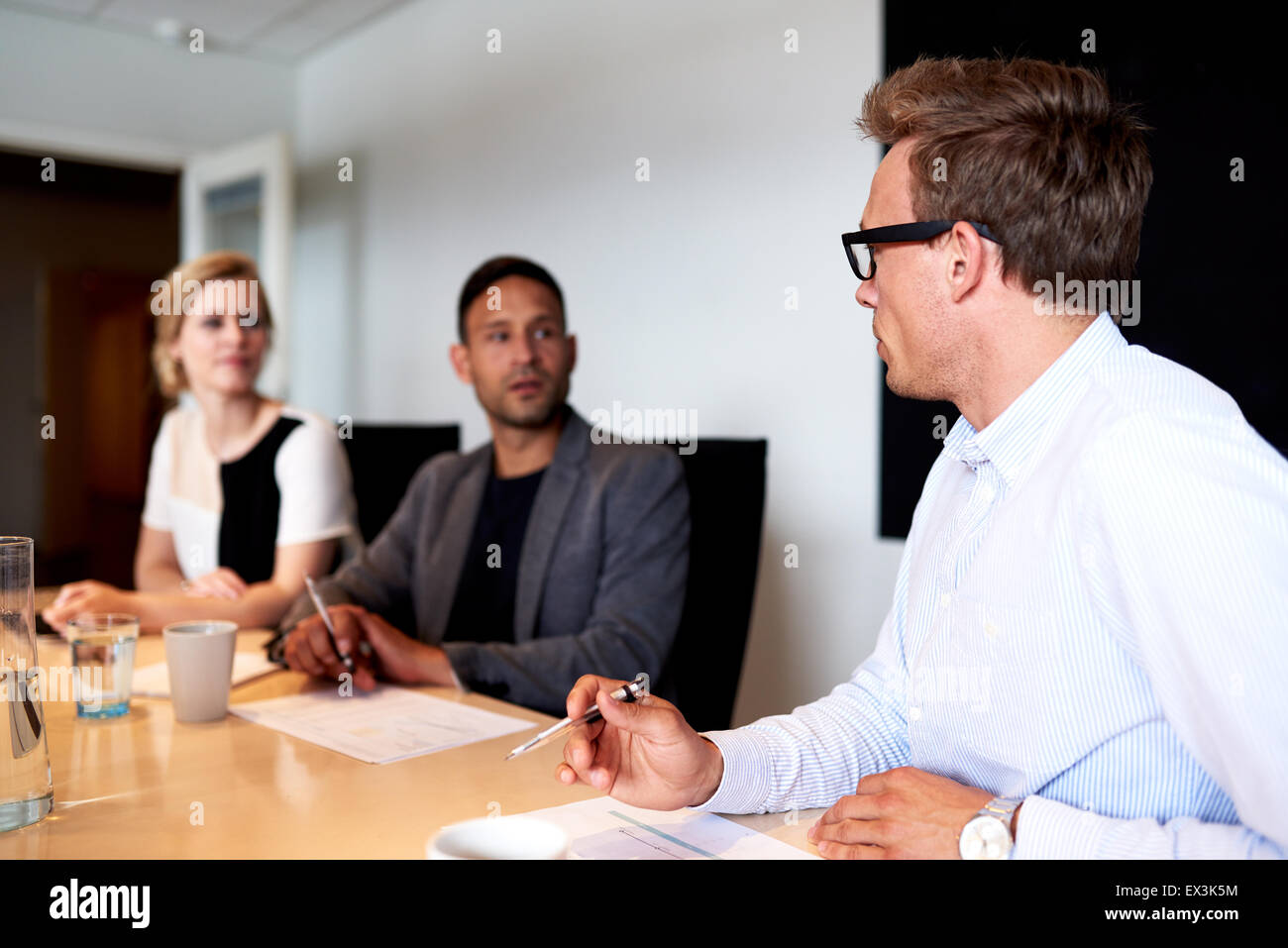 Young executives facing eachother during a meeting in conference room - Stock Image
