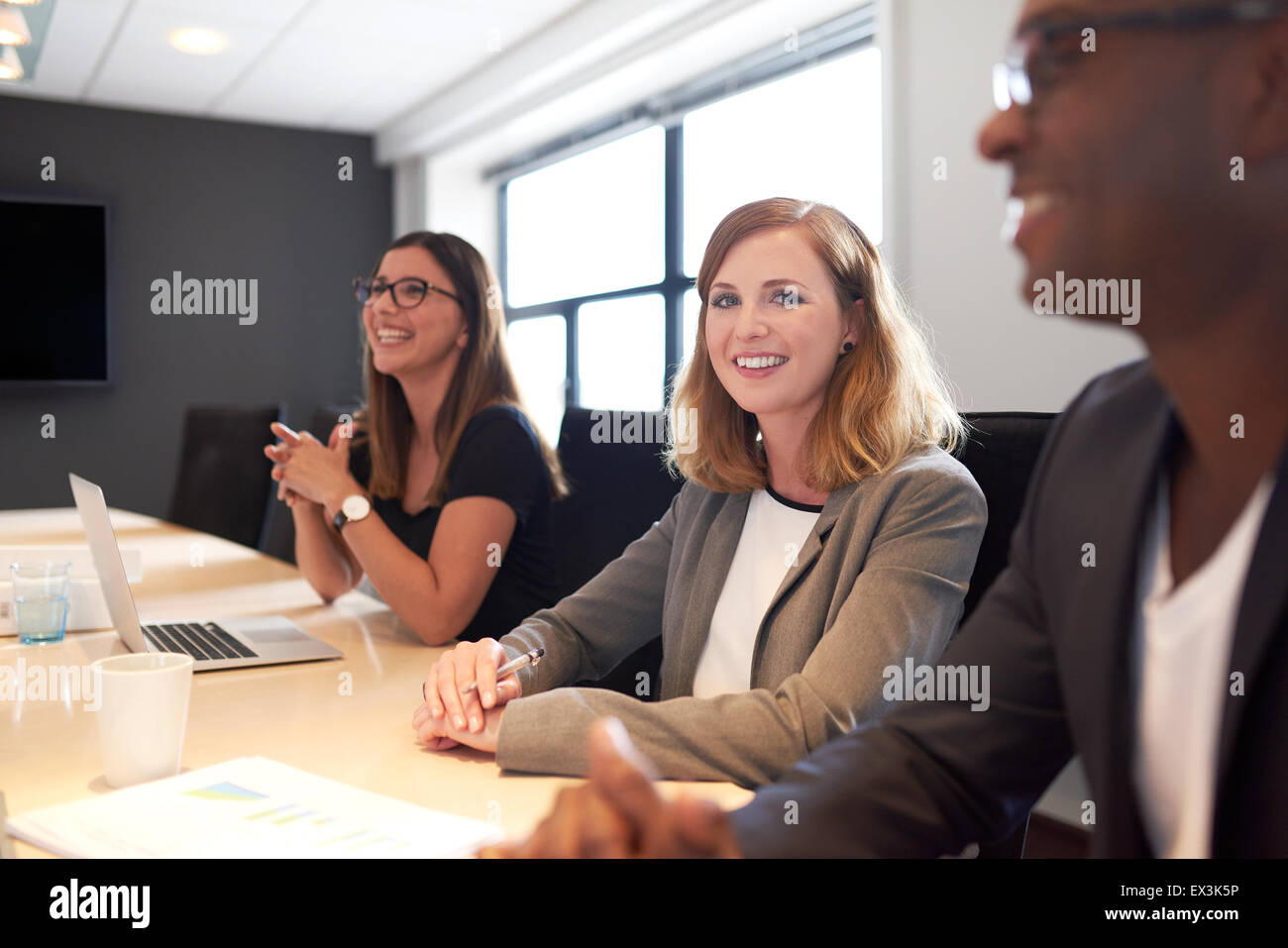 Young white female executive smiling at camera with hands clasped during meeting in conference room - Stock Image