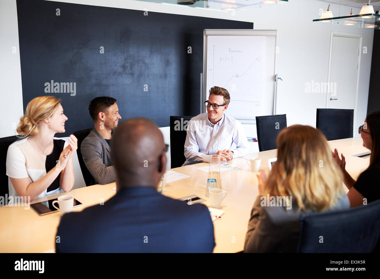 White male executive receiving applause from colleagues during a meeting - Stock Image