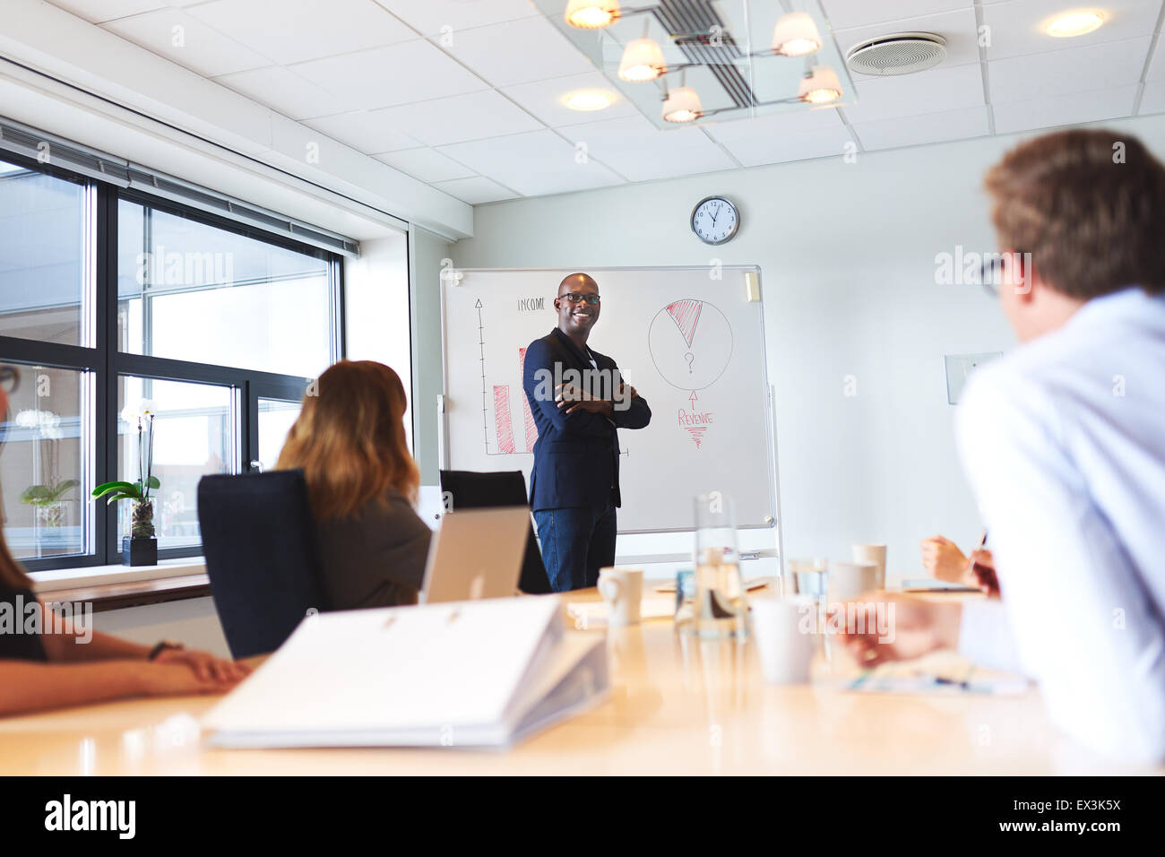 Black male executive smiling with arms crossed standing next to whiteboard in meeting - Stock Image