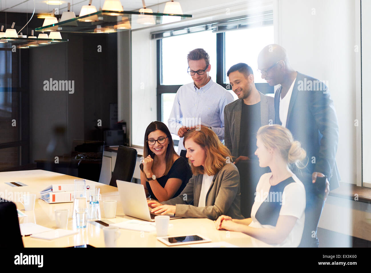 Group of young executives in conference room gathered together looking at laptop - Stock Image