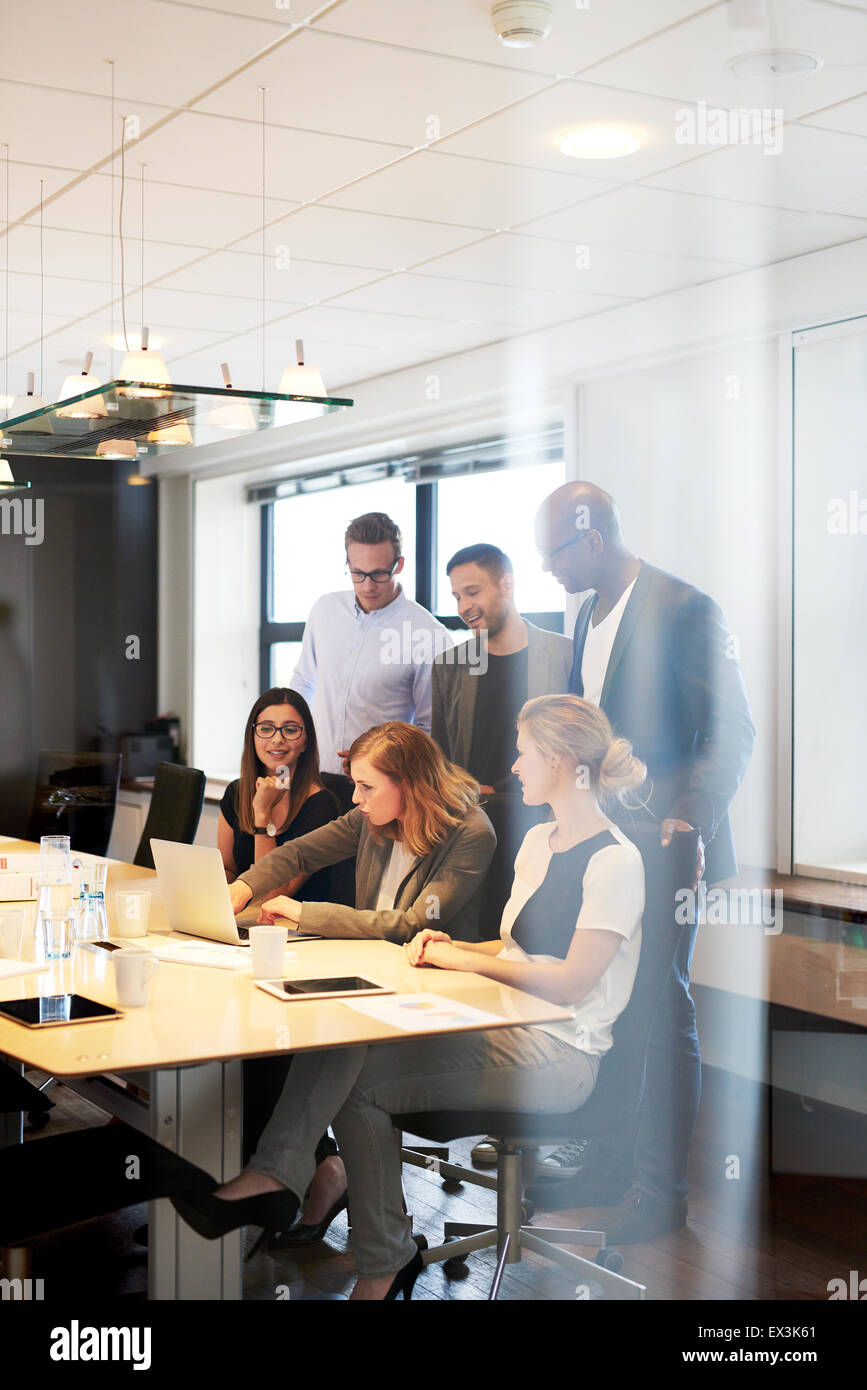 Group of executives gathered in conference room looking at laptop. - Stock Image