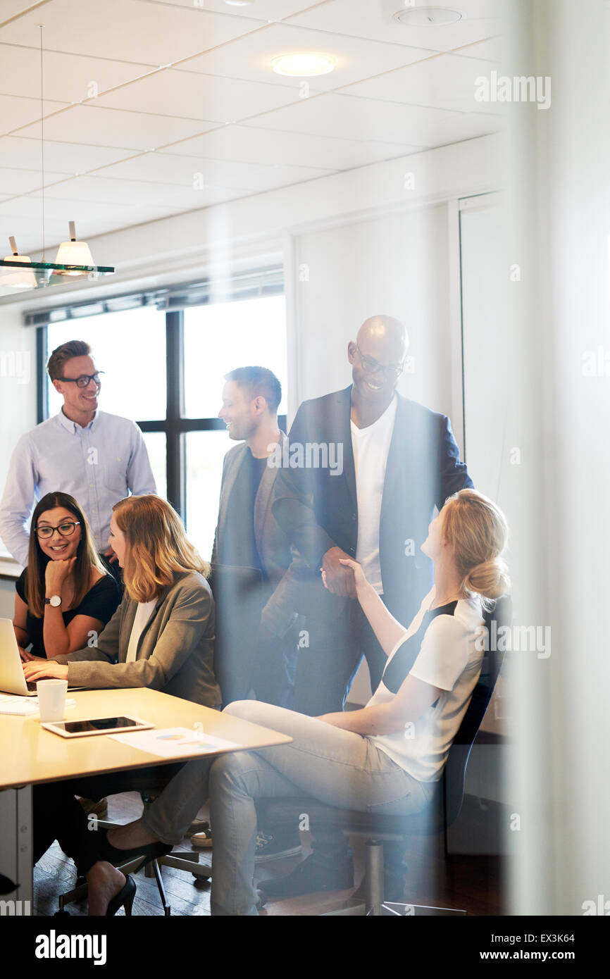 Group of young executives gathered and socializing in conference room - Stock Image
