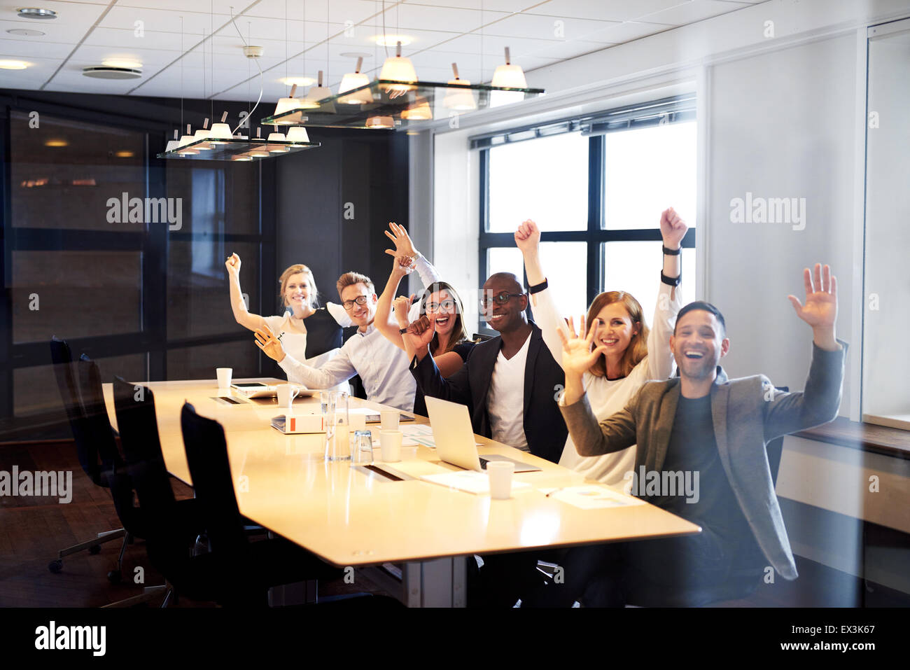 Group of young executives sitting at conference table posing with arms in air for camera. - Stock Image
