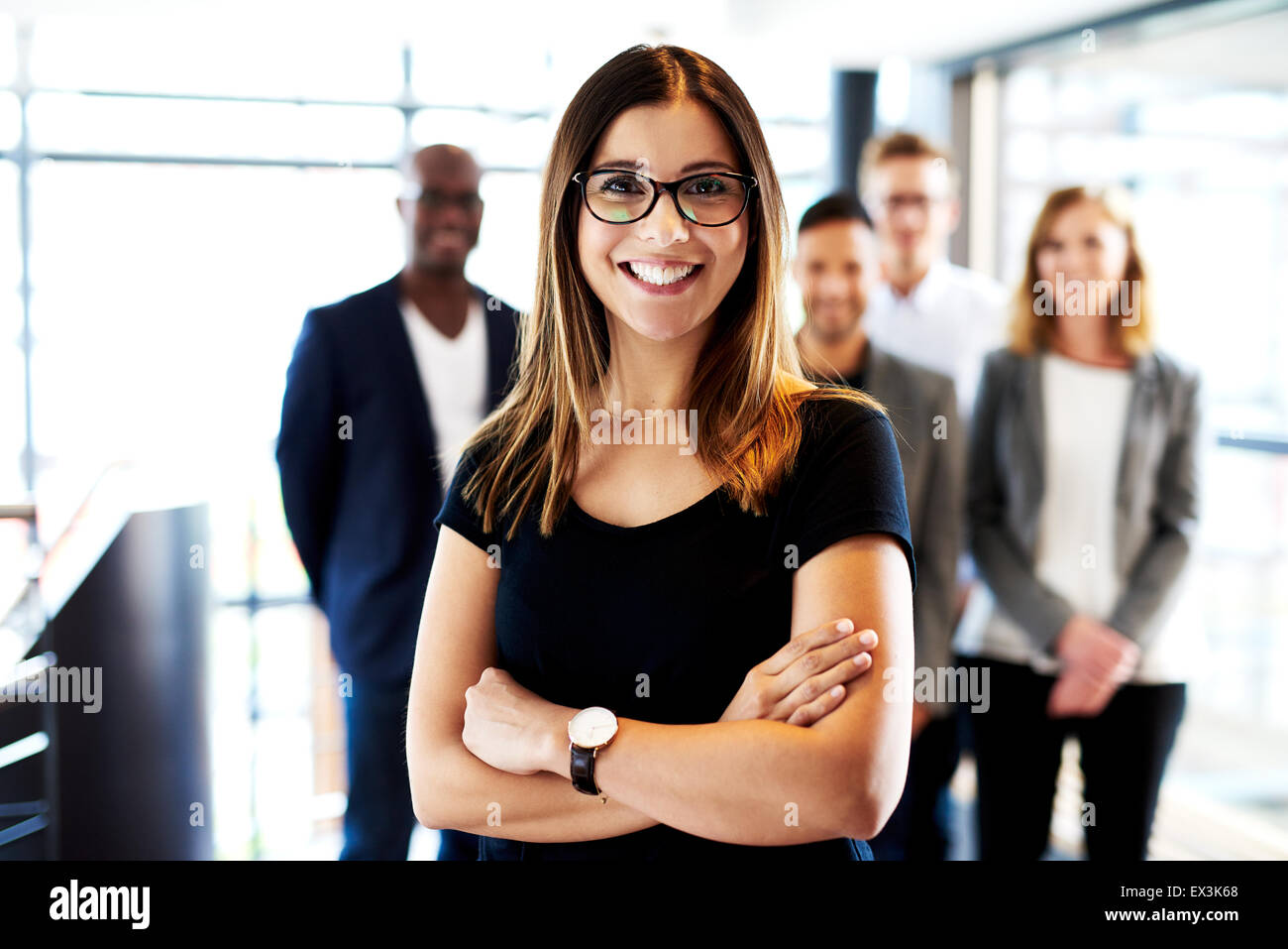 Young white female executive standing in front of colleagues with arms crossed and smiling - Stock Image