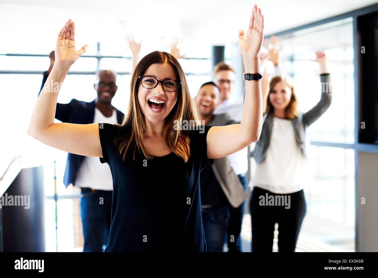 Young white female executive standing in front of colleagues with their arms raised up. - Stock Image