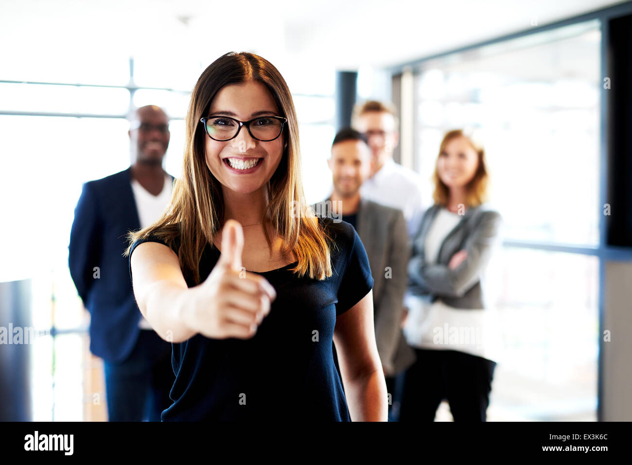 Young white female executive standing in front of colleagues making thumbs up sign. - Stock Image