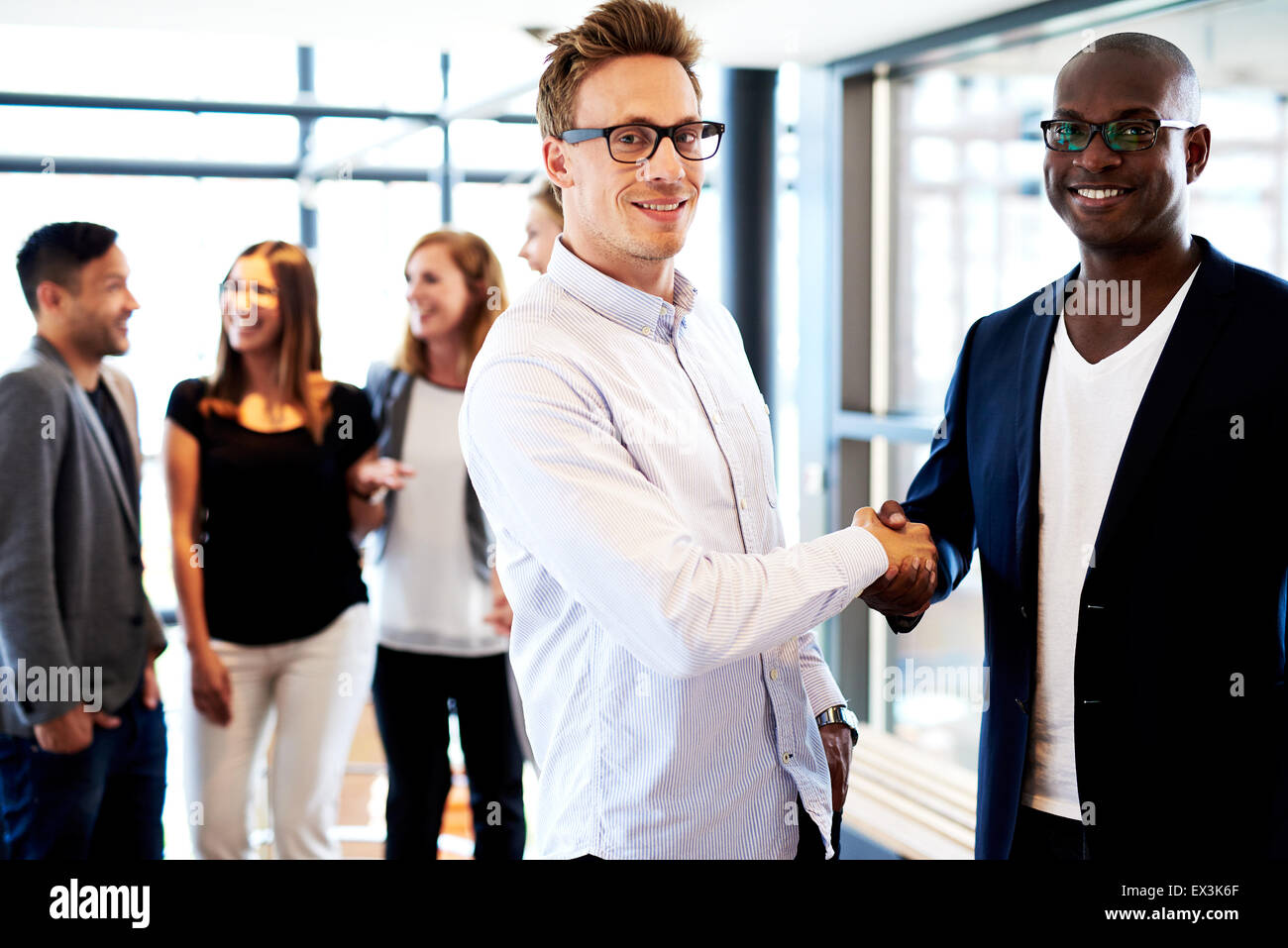 Black male executive and white male executive shaking hands looking at camera, colleagues in background - Stock Image