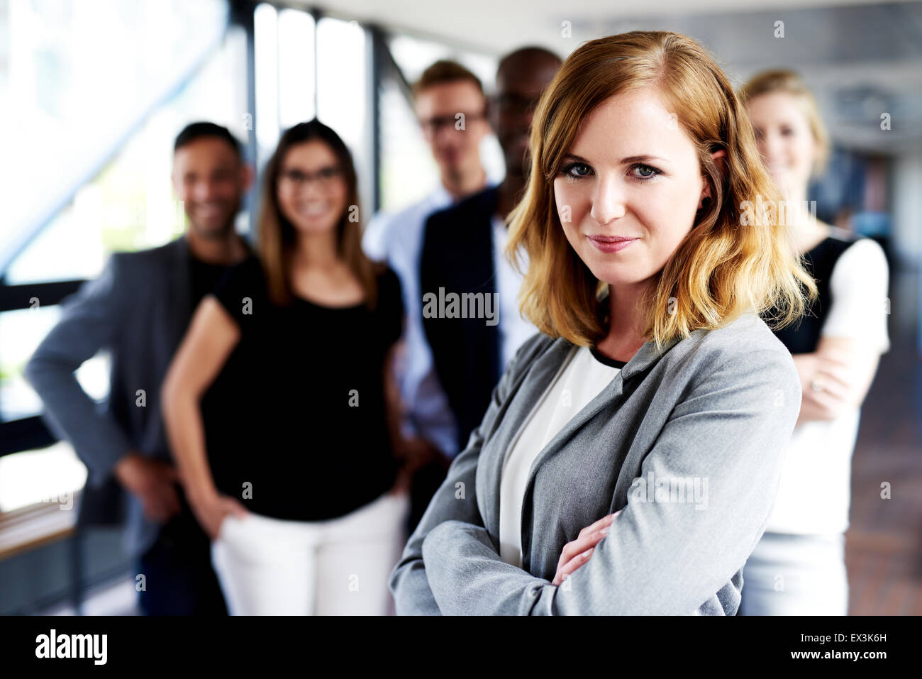 Young white female executive with arms crossed standing in front of colleagues grinning at camera - Stock Image