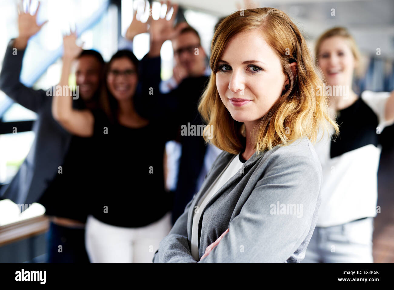 Female white executive standing in front of colleagues with their arms in air - Stock Image