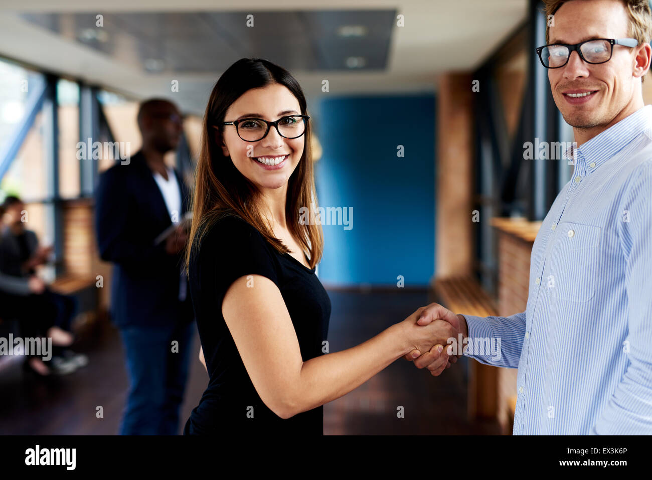 White female and white male executives shaking hands and smiling at camera - Stock Image