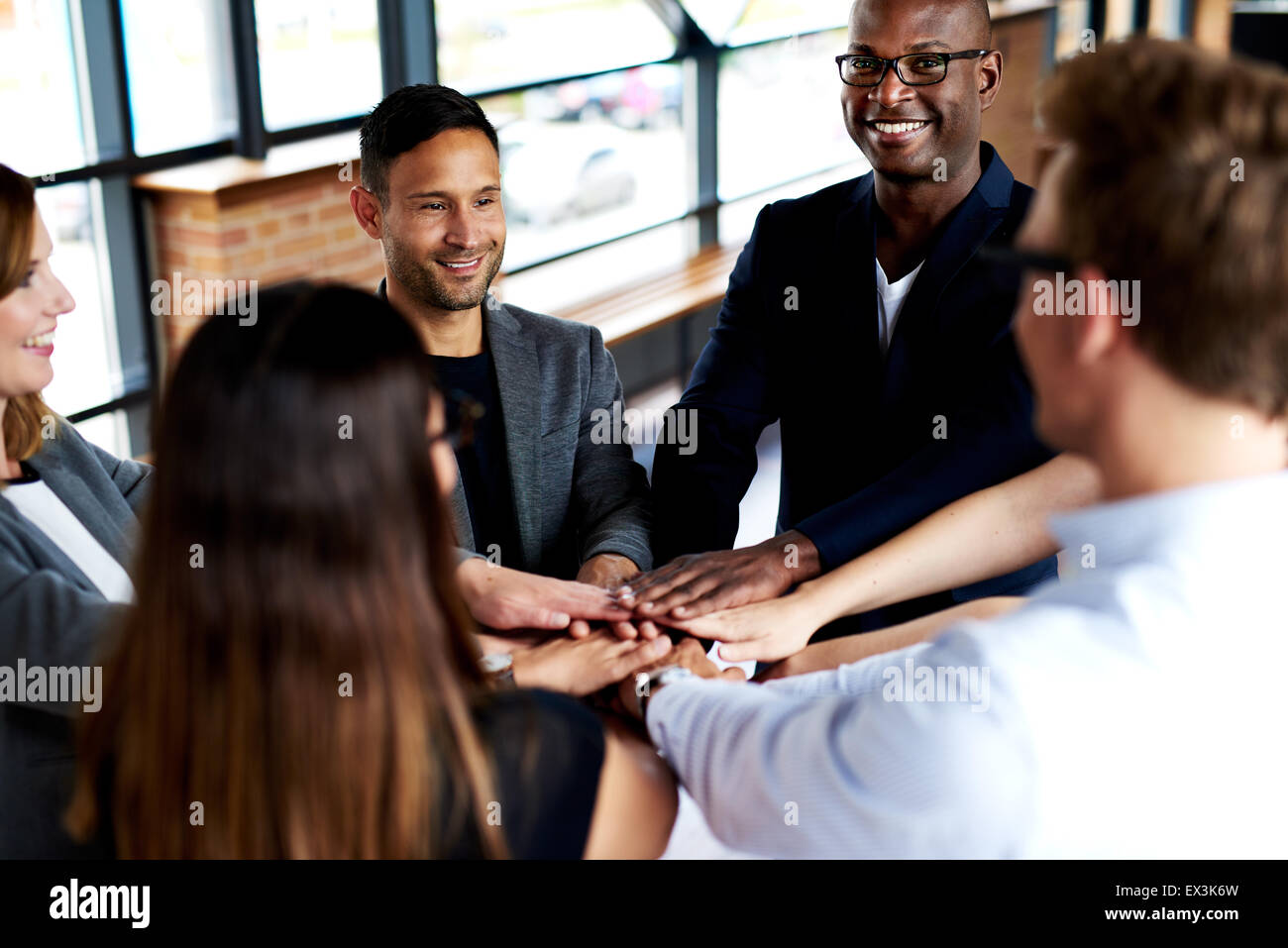 Group of young executives smiling and standing together with hands together - Stock Image