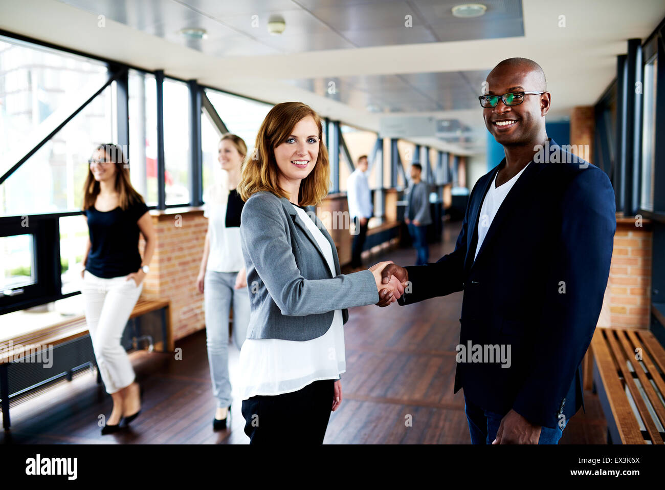 White female executive and black male executive shaking hands in hallway and smiling at camera - Stock Image
