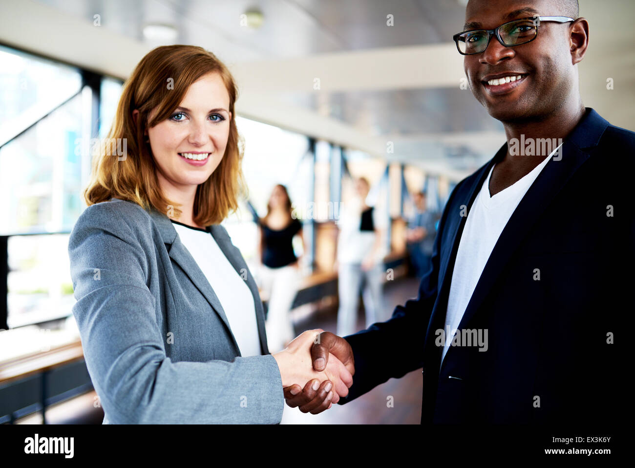 Close up of colleagues shaking hands smiling at camera - Stock Image