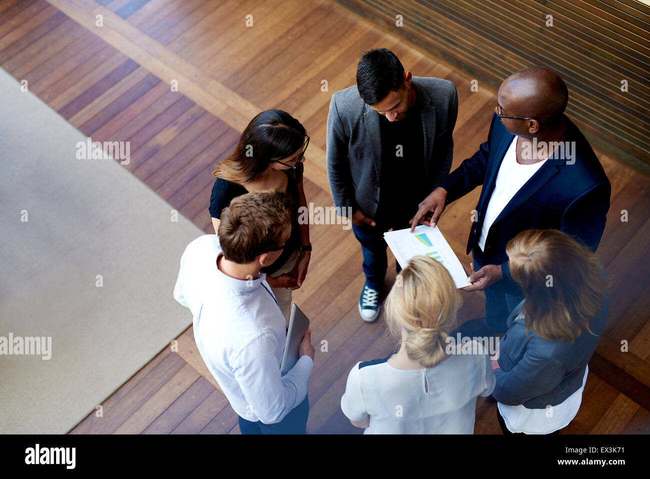 View looking down at colleagues standing in a circle looking at charts on paperwork - Stock Image
