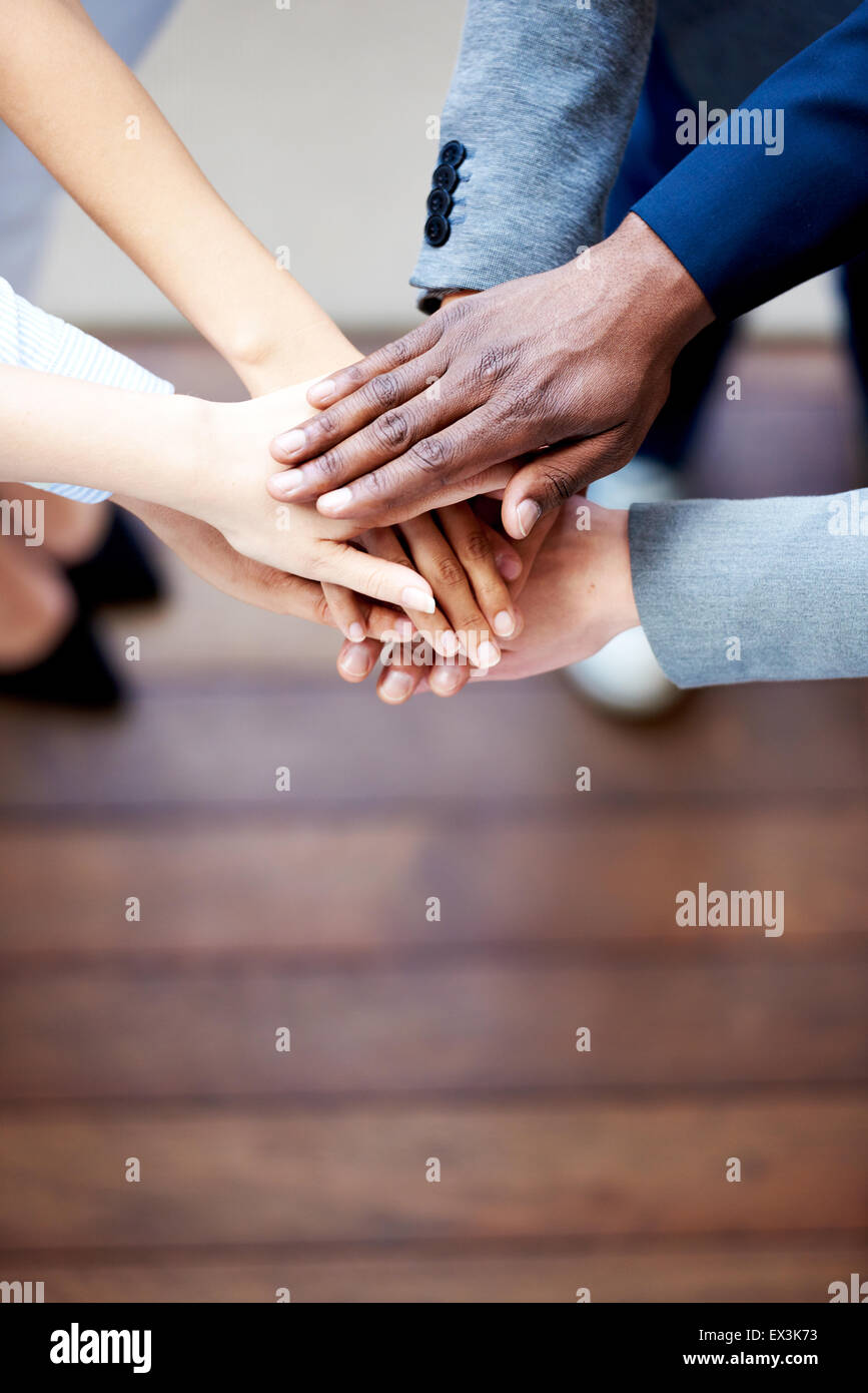 Close up of colleagues' hands clasped together - Stock Image