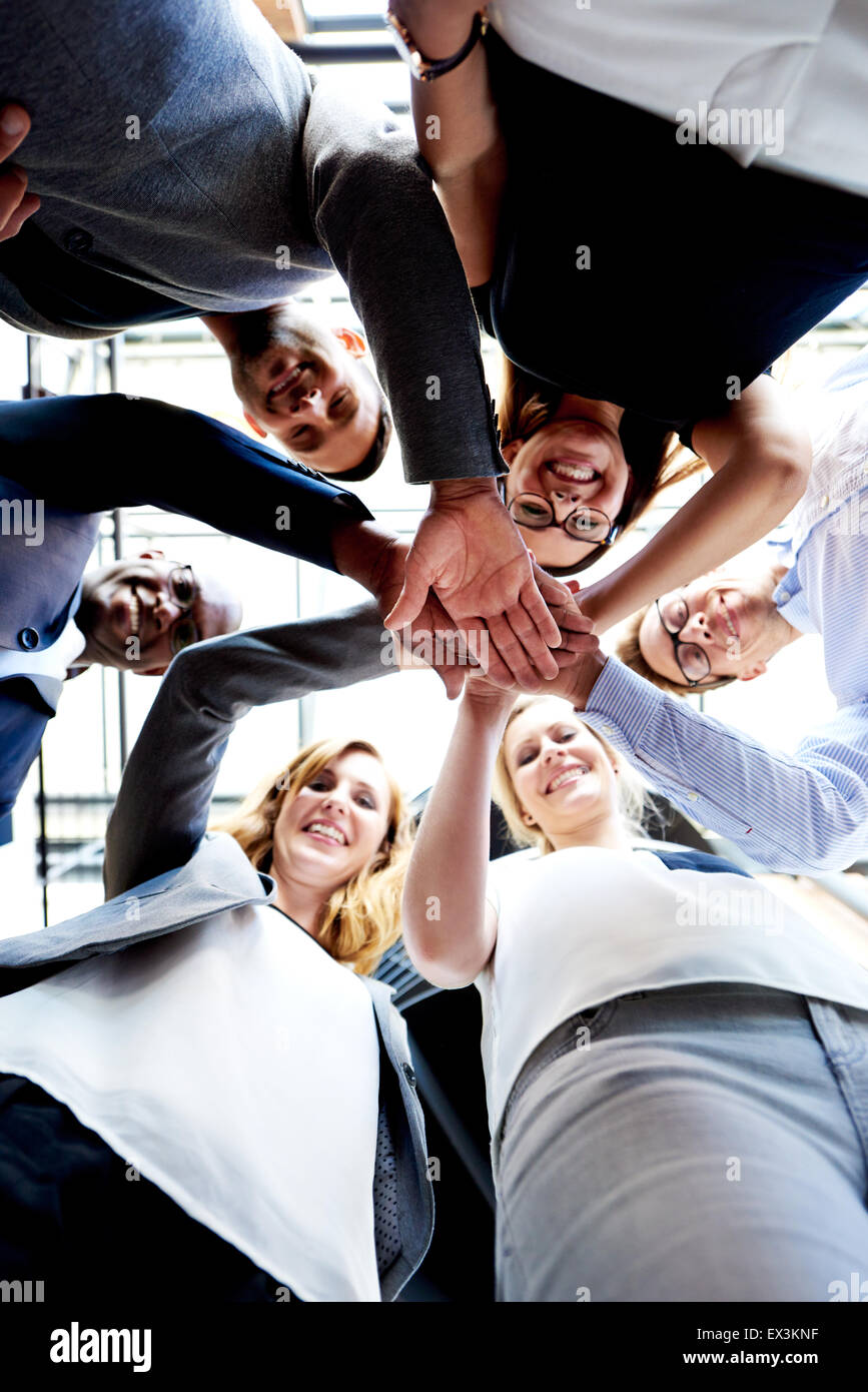 Co-workers standing in a circle hands together looking down at camera - Stock Image