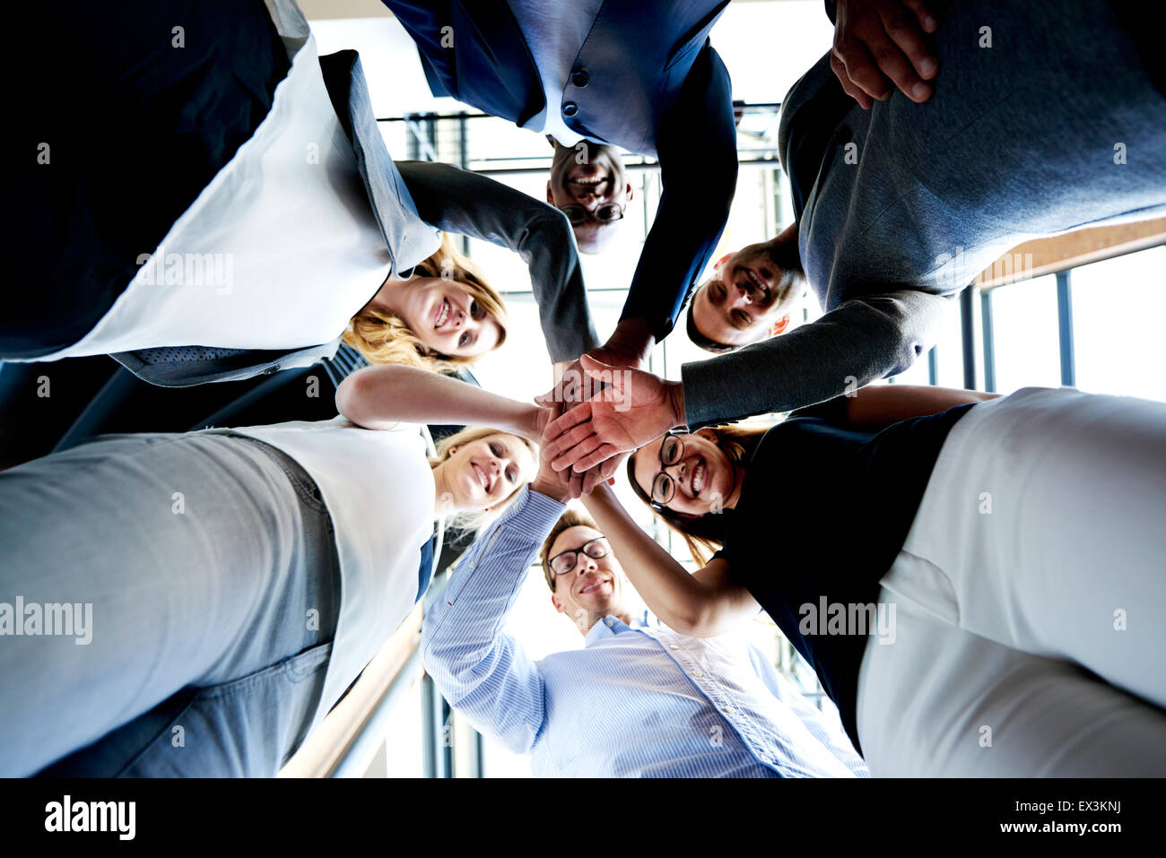 Group of young executives standing in a circle with hands together looking down. - Stock Image