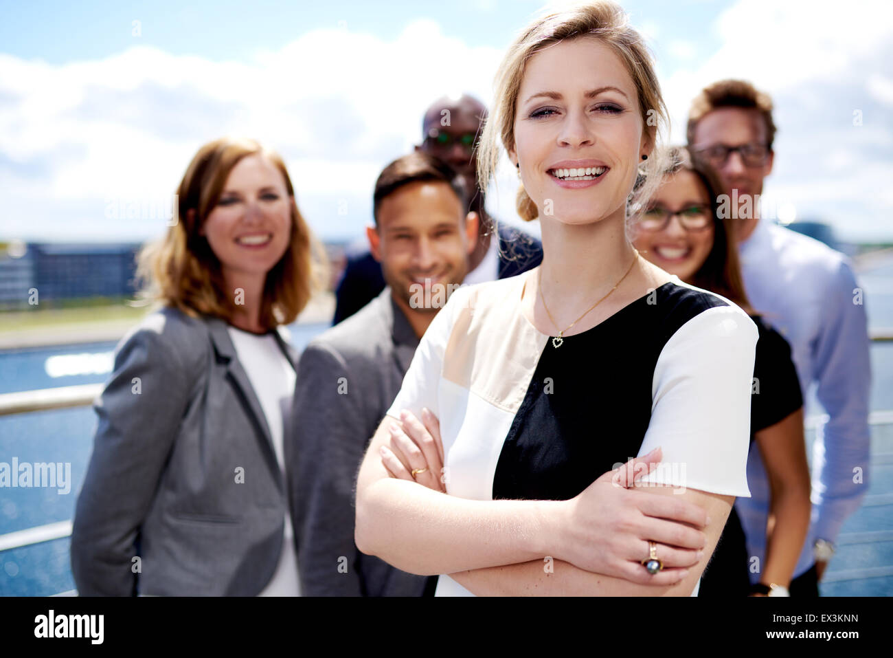 White female executive standing in front of colleagues with arms crossed smiling. - Stock Image