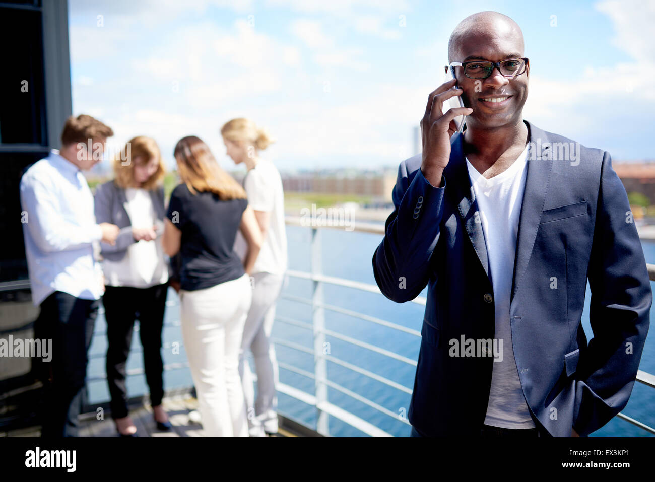 Black male executive smiling holding cellphone to ear and standing with hand in pocket - Stock Image