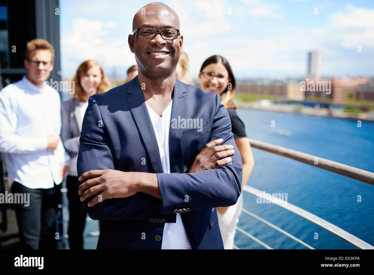 Black male executive standing with arms crossed in front of colleagues - Stock Image