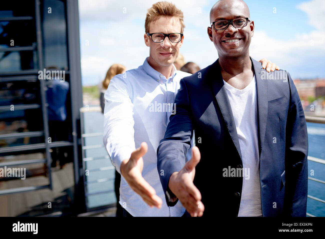 Black male colleague and white male colleague standing together smiling with hands stretched out - Stock Image