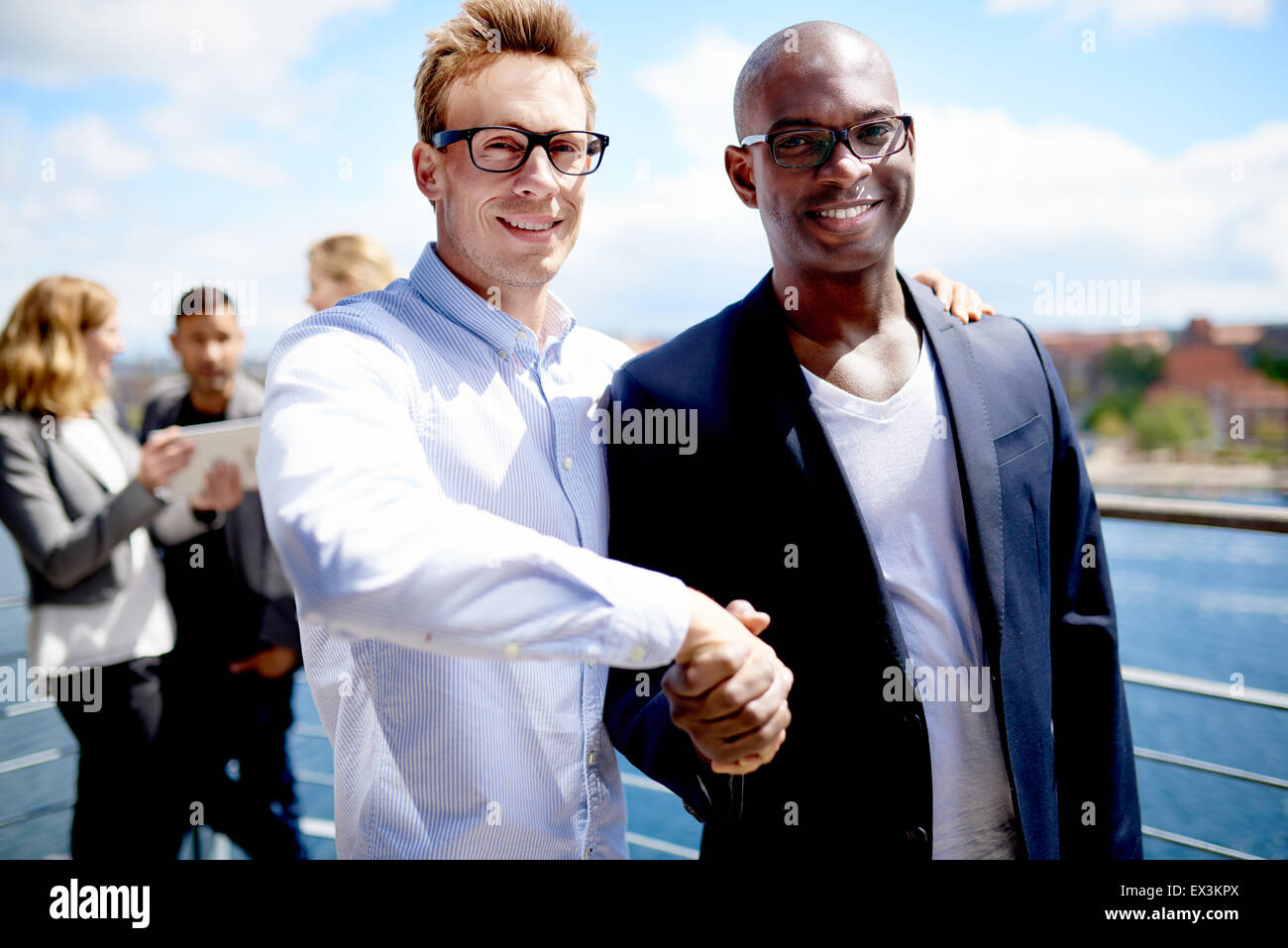Black male colleague and white male colleague smiling at camera and shaking hands - Stock Image