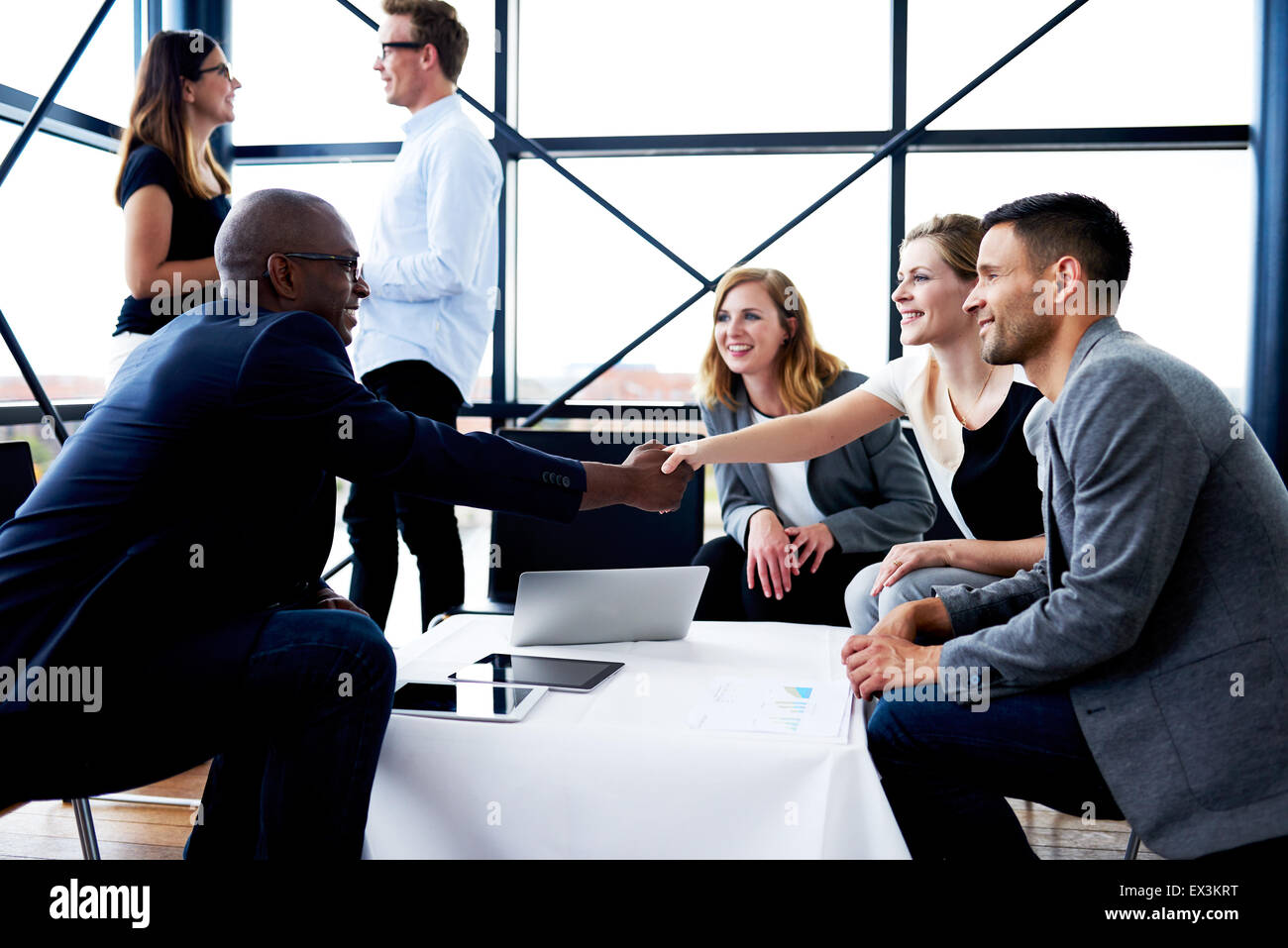 Black male executive sitting and shaking hands with white female colleague - Stock Image