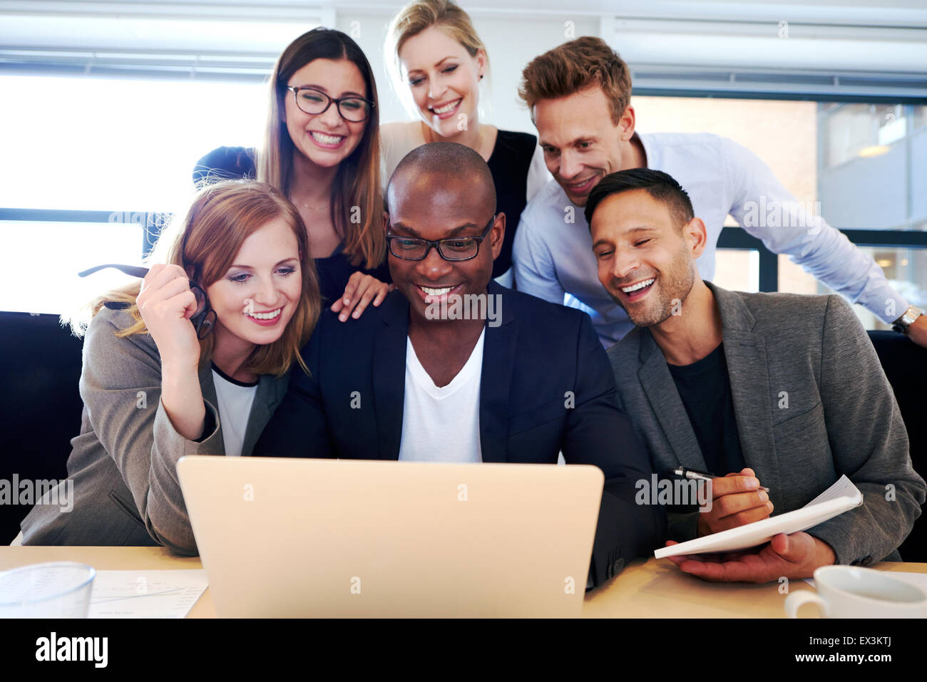 Group of executives smiling and gathered together looking at laptop - Stock Image
