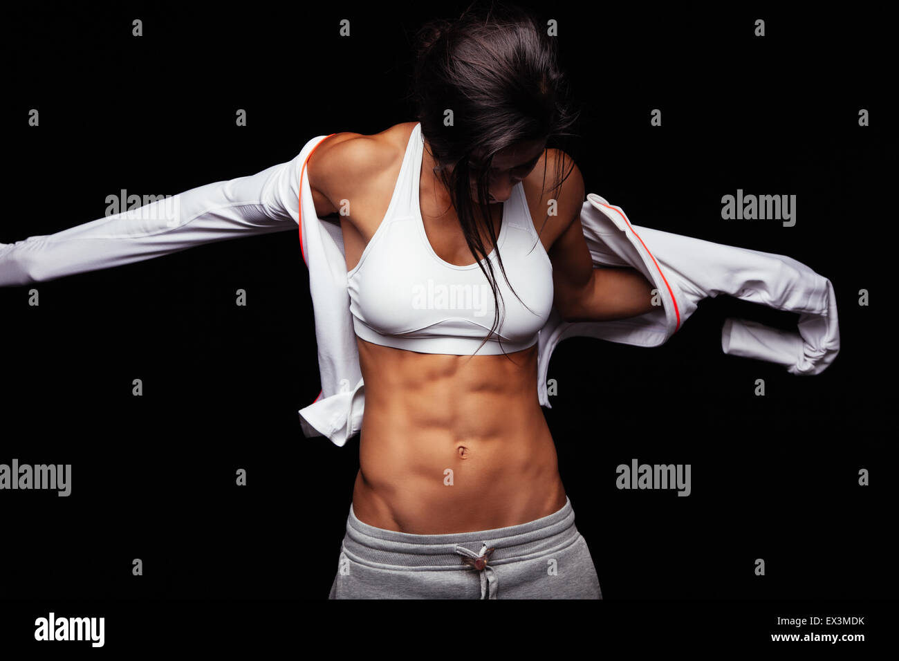 Image of muscular young woman wearing sports jacket. Getting ready for workout on black background - Stock Image