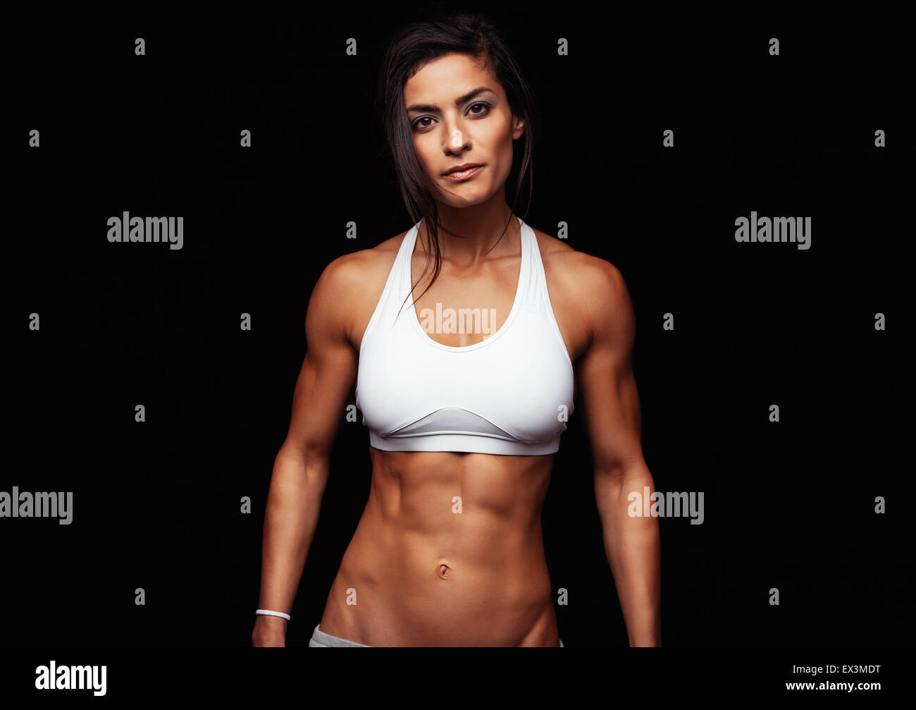 Portrait of fit young woman posing wearing sports bra against black background. Determined sportswoman in studio. - Stock Image