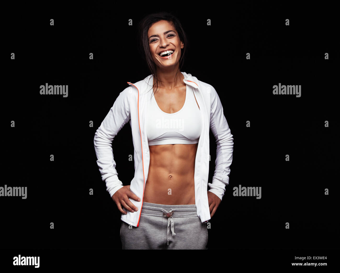 Smiling sportswoman in sportswear on black background. Caucasian fitness model looking happy with her hands on hips. - Stock Image