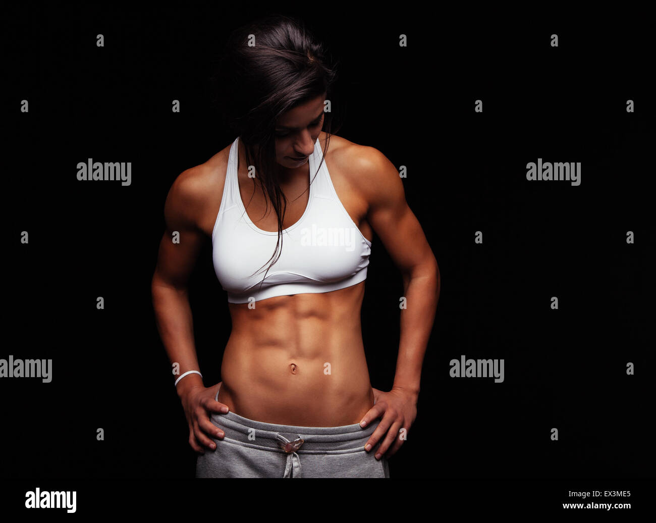 Fit young woman in sportswear looking down while standing with her hands on her hips. Muscular female model posing - Stock Image