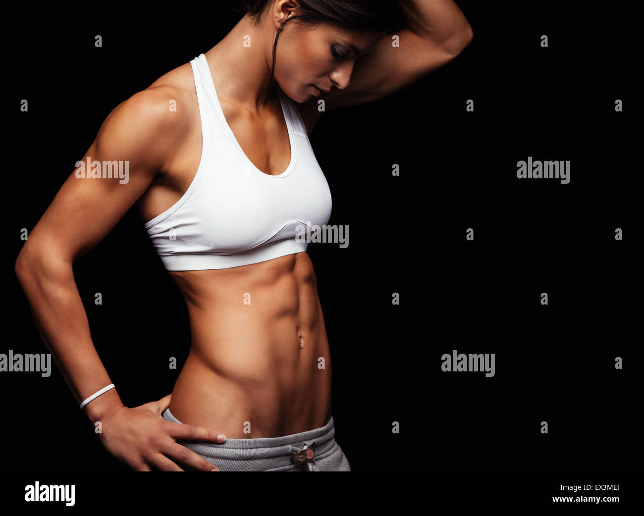 Cropped shot of fit woman's torso with her hands on hips. Female with perfect abdomen muscles posing on black - Stock Image