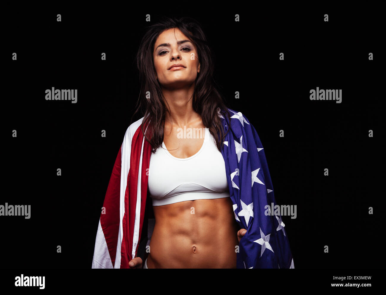 Portrait of proud female athlete wrapped in American Flag against black background. Muscular young woman looking - Stock Image