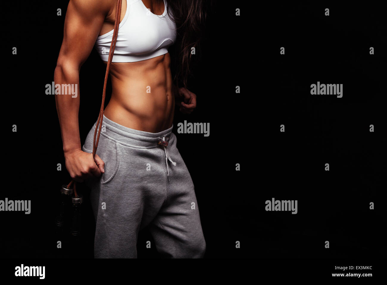Close up of young woman's torso. Perfect abdomen muscles of a female athlete holding skipping ropes on black - Stock Image