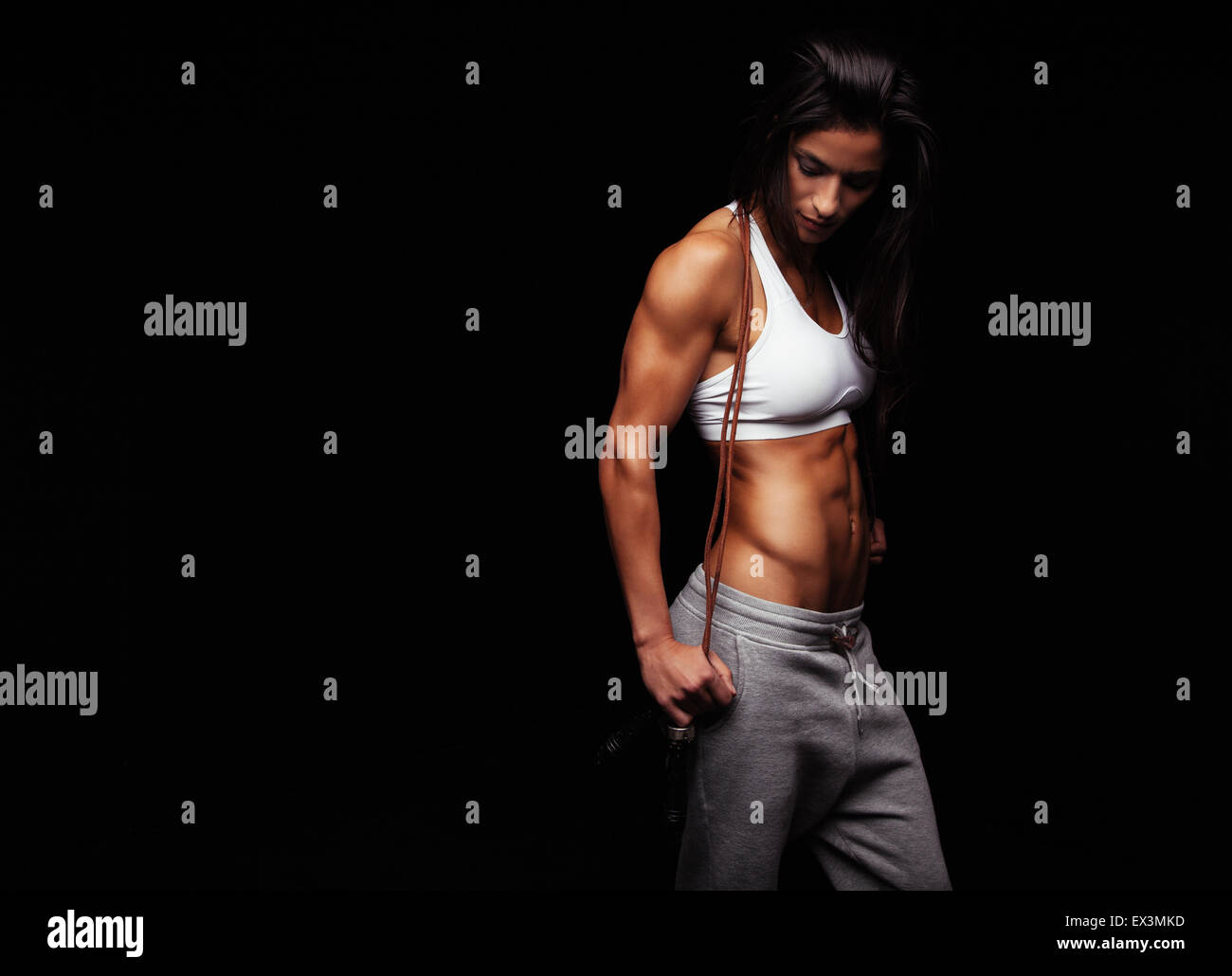 Shot of young female exercises with a jump rope looking down. Muscular woman with skipping ropes against black background, - Stock Image