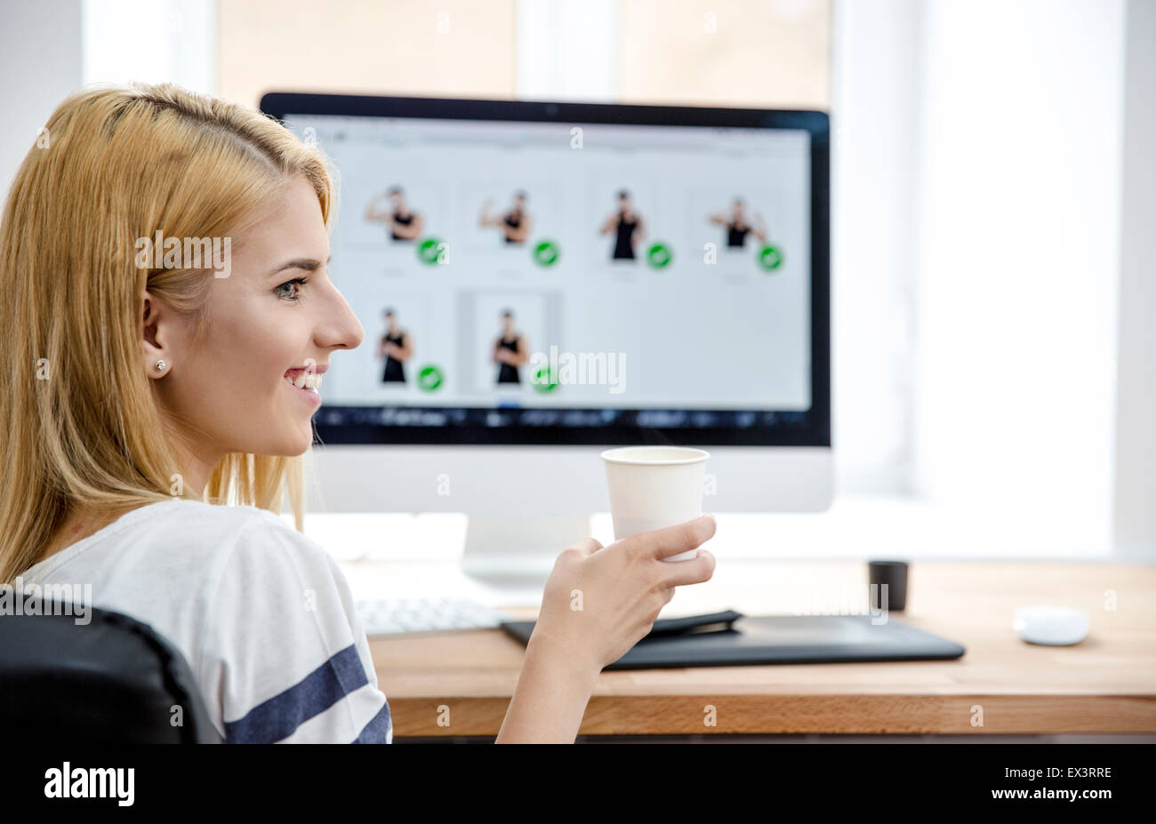 Happpy young woman sitting at the table in office and holding cup with coffee - Stock Image