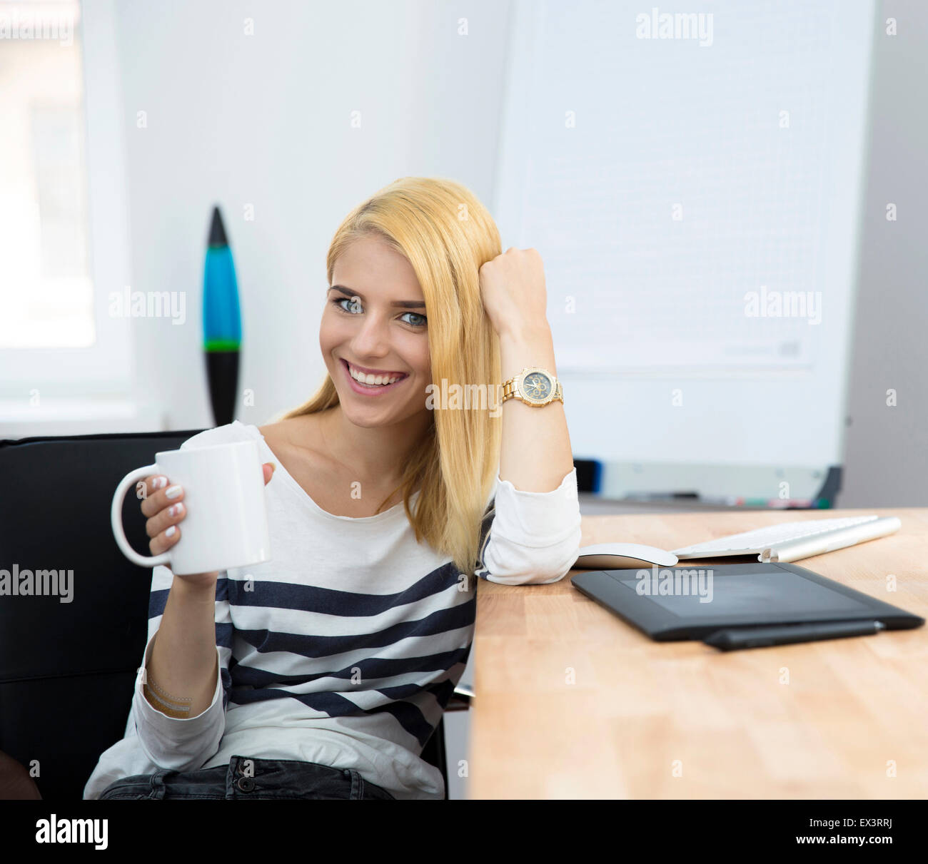 Smiling young female photo editor sitting at the table with cup of coffee in office and looking at camera Stock Photo