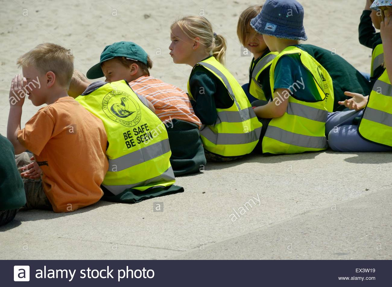 Young children sitting by the beach, some with safety jackets on with the slogan 'Be Safe, Be Seen' on the back Stock Photo
