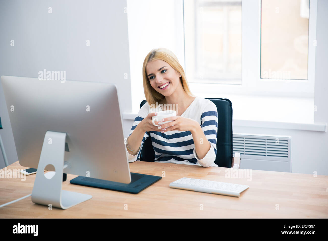 Happy female designer sitting at the table with desktop and drinking coffee in office - Stock Image