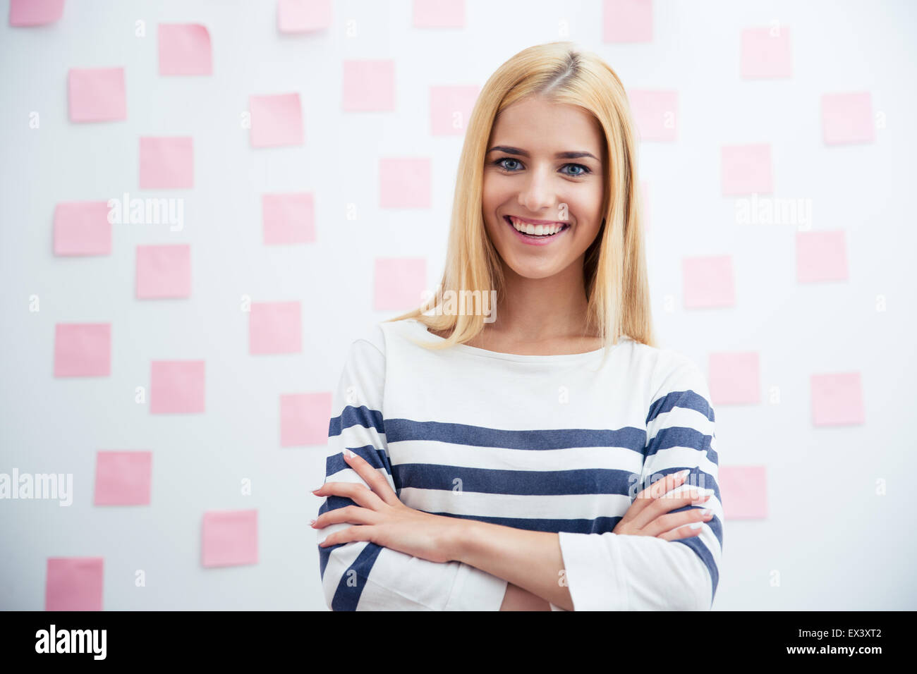 Smiling young casual girl standing with arms folded in office with stickers on background - Stock Image