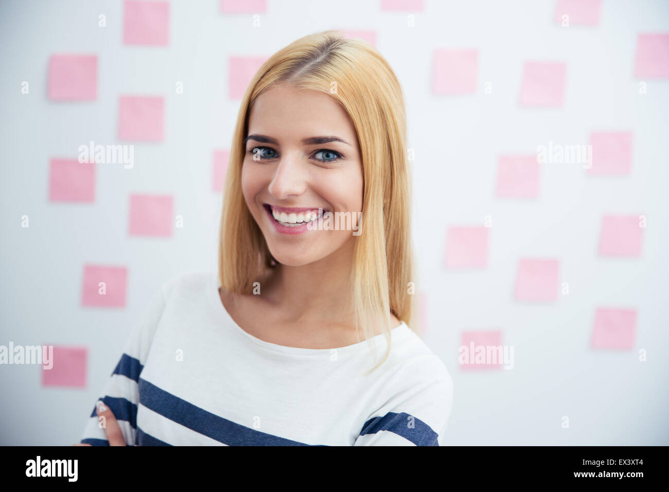 Cheerful young woman standing in office with stickers on background - Stock Image