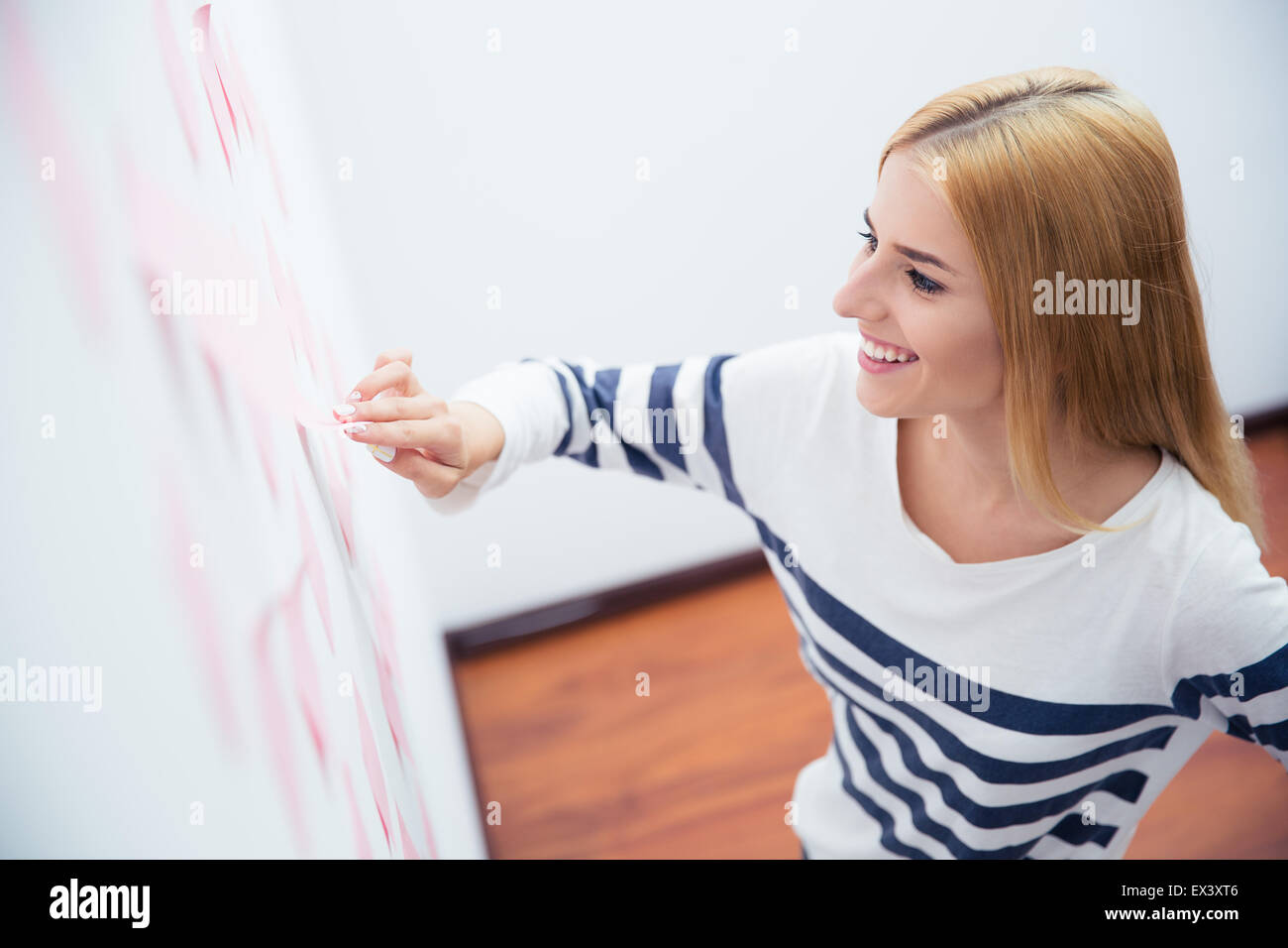 Happy casual girl looking at stickers on wall in office - Stock Image