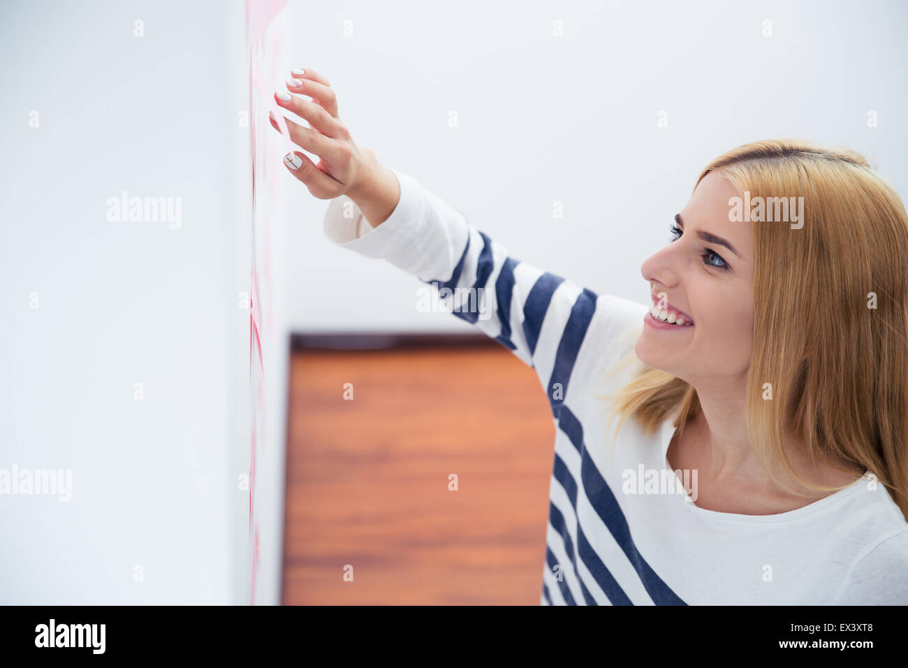Happy young woman reading stickers on gray wall in office - Stock Image