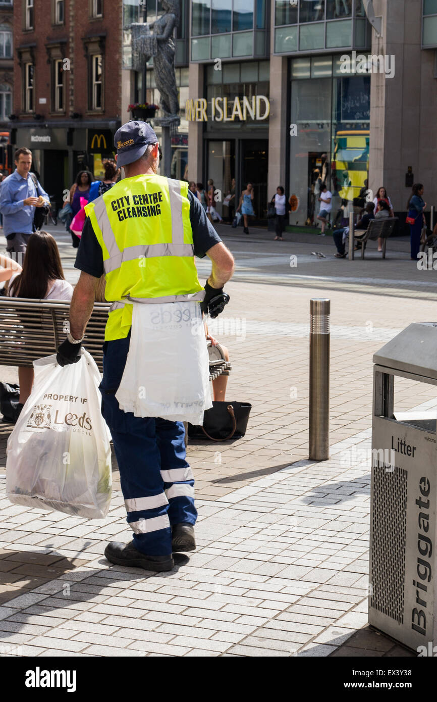 Worker from Leeds City Council City Centre Cleansing Team emptying bins and collecting rubbish on Briggate near - Stock Image