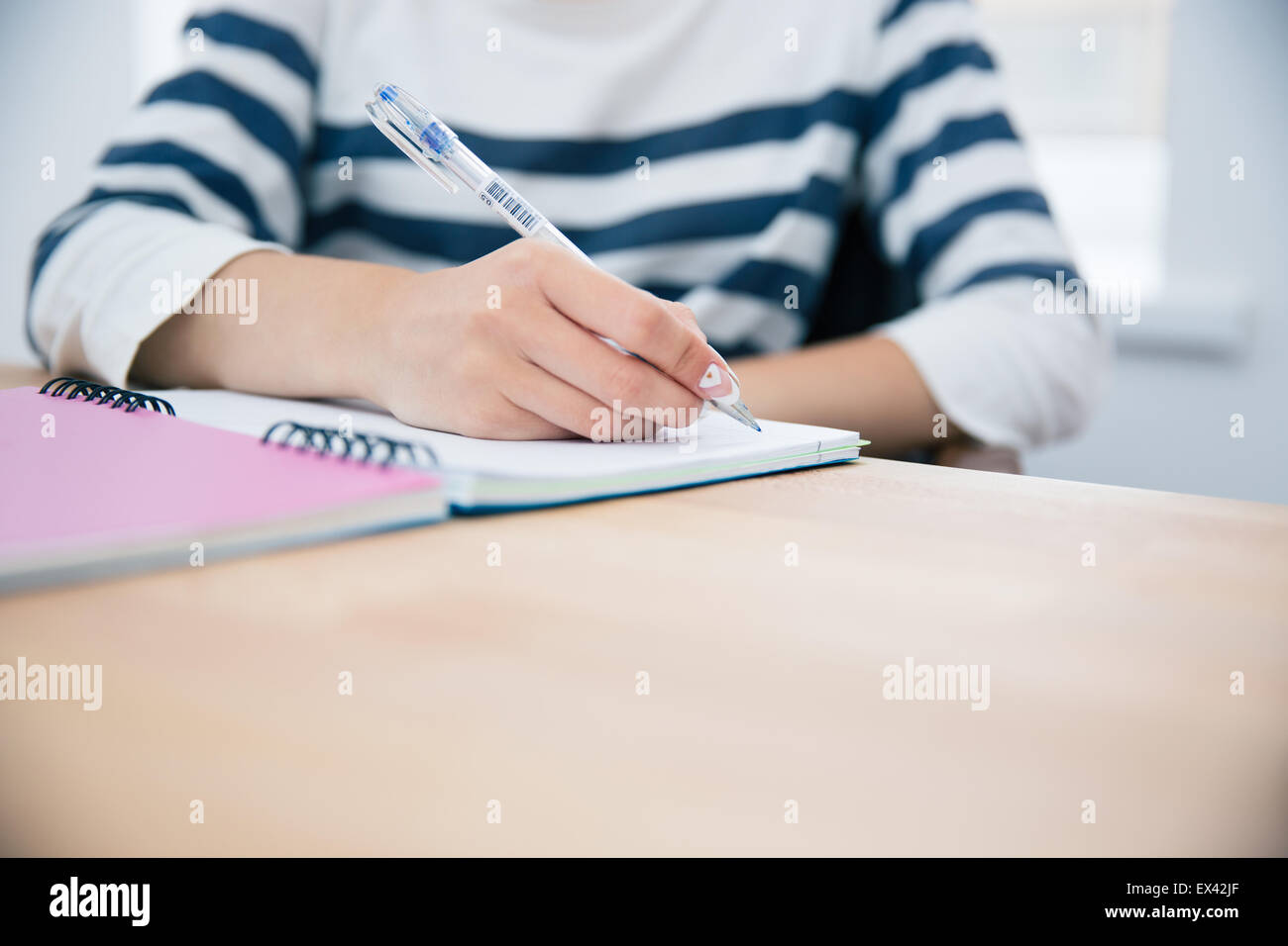CLoseup portrait of a woman writing in notepad at office - Stock Image