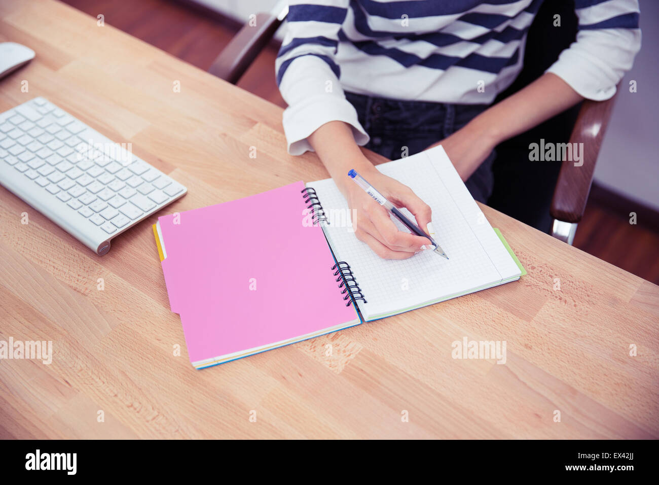 Closeup portrait of a casual woman writing notes in office - Stock Image